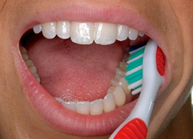 Place the toothbrush against your gumline at a 45-degree angle. Move the brush back and forth gently in short strokes.