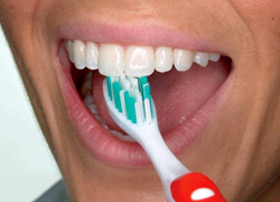 Use the top part of the brush to clean the inside surface of the top and bottom front teeth. Use a gentle up-and-down motion.